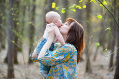 Young mother with her little baby in forest Stock Photo