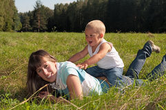 Young mother and her little baby are on meadow Royalty Free Stock Image