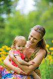 Young mother with her little baby on the meadow Royalty Free Stock Image