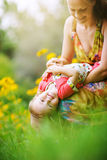 Young mother with her little baby on the meadow Royalty Free Stock Photography