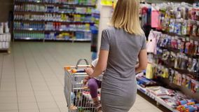 Young mother with her little baby sitting in a grocery cart in a supermarket is pushing the cart forward and choosing stock video