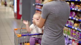Young mother with her little baby sitting in a grocery cart in a supermarket is pushing the cart forward walking and stock video footage