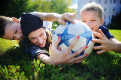 Young mother and her little boys playing a soccer game on sunny summer day royalty free stock photos