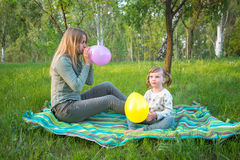 Young mother with her little daughter are blowing colored balloons royalty free stock images