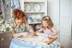 Young mother with her little daughter are cooking. A young mother with her little daughter are cooking on a kitchen Royalty Free Stock Images