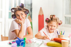 The young mother and her little daughter drawing with pencils at home Royalty Free Stock Images