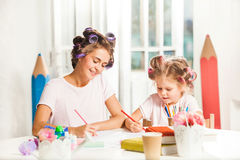 The young mother and her little daughter drawing with pencils at home Stock Image