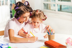 The young mother and her little daughter drawing with pencils at home Stock Images