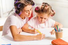 The young mother and her little daughter drawing with pencils at home Royalty Free Stock Image