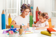 The young mother and her little daughter drawing with pencils at home Royalty Free Stock Photo