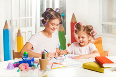 The young mother and her little daughter drawing with pencils at home Stock Photography