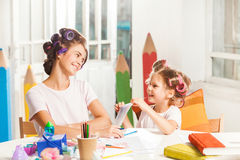 The young mother and her little daughter drawing with pencils at home Stock Photo