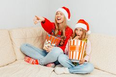 Mom and her little daughter, dressed in Santa Claus hats, watch stock photography