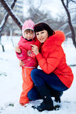 Young mother and her little daughter enjoying beautiful winter d Royalty Free Stock Photos