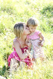 Mother and her little daughter on the grass outdoors Royalty Free Stock Photo