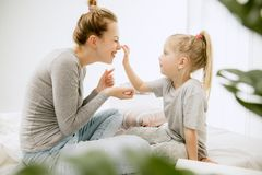 Young mother and her little daughter hugging and kissing on bed. Young mother and her little daughter at home at sunny morning. Soft pastel colors. Happy family stock photos