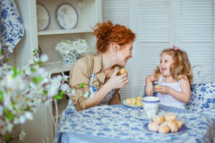 Young mother with her little daughter are laughing. A young mother with her little daughter are laughing on a kitchen Royalty Free Stock Images