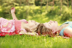 Young mother and her little daughter lie on the grass Stock Photos