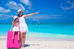 Young mother and her little daughter with luggage on tropical white beach Stock Photos