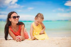 Young mother and her little daughter lying at Royalty Free Stock Images