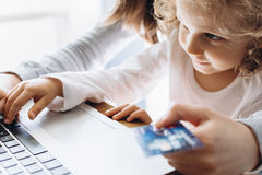 Young mother and her little daughter making online shopping Stock Photos