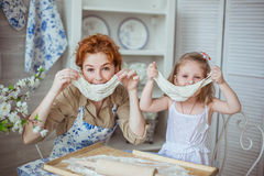 Young mother with her little daughter play with a dough. Portrait of a young mother with her little daughter play with a dough on a kitchen. Their noses is dirty Stock Photos