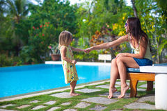 Young mother and her little daughter play near the Stock Photography