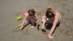 Young mother with her little daughter play on a sandy beach, build figures and castles from sand.  stock footage