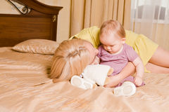 Young mother with her little daughter playing on bed at home Stock Photo