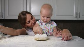 Young mother and her little daughter preparing dough on the table. Baker prepares the dough. Family girls having fun. Slowmotion shot stock footage