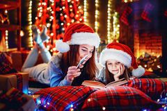Young mother with her little daughter reading a book while sitting under decorated Christmas tree on the floor royalty free stock photo