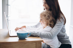 Young mother and her little daughter sitting using a laptop Stock Images