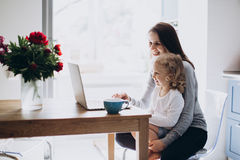Young mother and her little daughter sitting using a laptop Stock Photo