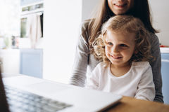 Young mother and her little daughter sitting using a laptop Royalty Free Stock Photography