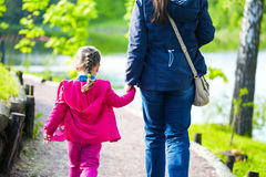 Young mother and her little daughter walking near the pond in the park Royalty Free Stock Images
