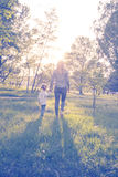 Young mother and her little daughter walking through park Stock Photography