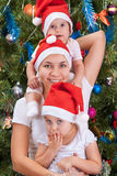 Young mother and her little daughters near to a Christmas tree Royalty Free Stock Image