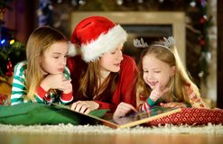 Young mother and her little daughters reading a book by a Christmas tree in cozy living room in winter royalty free stock images