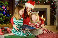 Young mother and her little daughters reading a book by a Christmas tree in cozy living room in winter royalty free stock photography