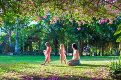Young mother with her little daughters sitting in. Young mother and her little daughters sitting in the lush garden and enjoy the rest Stock Photo