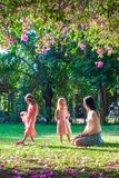 Young mother with her little daughters sitting in. Young mother and her little daughters sitting in the lush garden and enjoy the rest Royalty Free Stock Photo