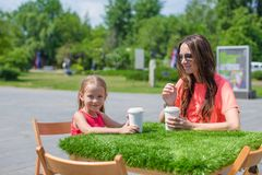 Young mother and her little girl at outdoor cafe Stock Photos