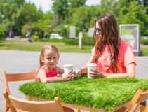 Young mother and her little girl at outdoor cafe Royalty Free Stock Images
