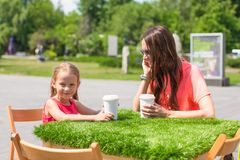 Young mother and her little girl at outdoor cafe Royalty Free Stock Photography