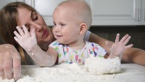 Young mother and her little kid preparing dough on the table. Little baby playing with flour. Baker prepares the dough stock video footage
