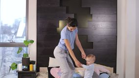 A young mother and her little one-year-old son are jump at home on the bed. A young cheerful mother and her little one-year-old son are having fun at home on stock video footage