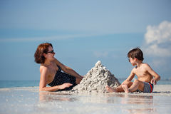 Young mother and her little son building sand Stock Image