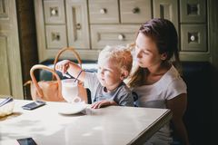 Young mother and her little son in a cafe. Young mother and her little son having lunch in a cafe Royalty Free Stock Photo