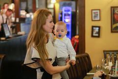 Young mother and her little son in a cafe. Mother with child in arms. Stock Photography