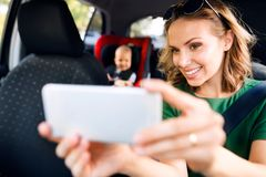 Young mother with smartphone and baby boy in the car. Young mother with her little son in the car. Woman taking selfie with a smartphone Stock Photo